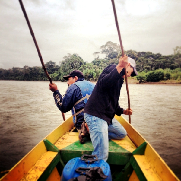 Locals work hard to navigate the jungle river.